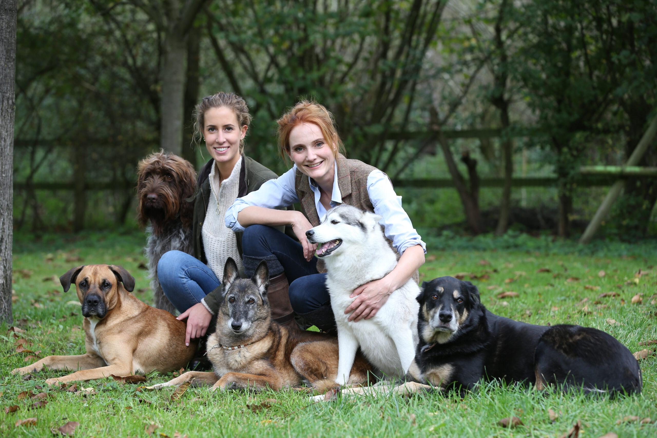 Hundetrainerinnen Ramona und Julia mit einer Hundegruppe auf der Wiese der Hundeschule Body Talk in Oberhausen